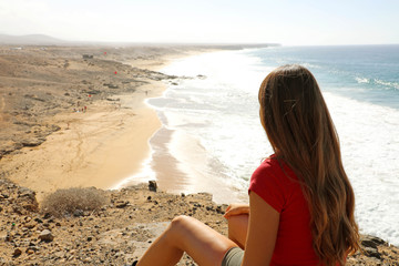 Calm, relax ,mind reset concept. Young woman sitting on top of the cliff, breathing fresh air and enjoying view ocean waves on Fuerteventura coast.