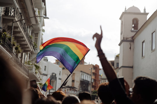 The rainbow pride flag waving at sunset in the middle of the lgbtq+ parade in Panama