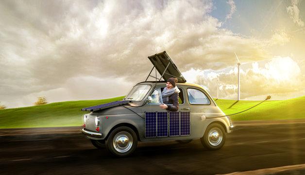 Frau fährt in Ihrem Elektroauto übers land und lädt diese mittels Solarpanels