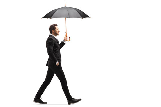 Handsome businessman walking with an open umbrella