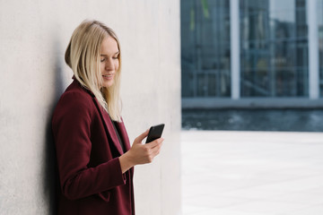 Blond businesswoman using smartphone, leaning on a wall, looking down Wall mural