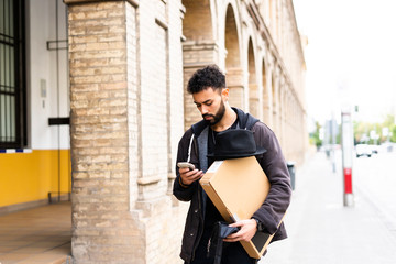 Young man with hat and parcel looking at cell phone in the city