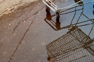 an empty grocery basket from the supermarket and its reflection in the rain in the Parking lot