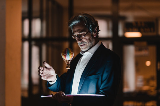 Senior businessman with tablet and floating hot-air balloon in office
