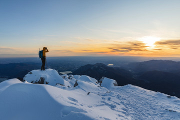 Mountaineer standing on top of a snowy mountain enjoying the view