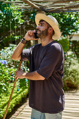 Man with broom using his smartphone outdoors