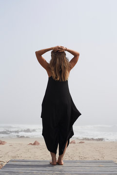 Rear view of woman standing at the ocean, Cape Cross, Namibia