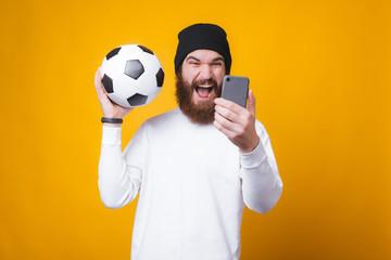 ชายหนุ่มมีเครากำลังถ่ายเซลฟี่และถือลูกฟุตบอลใกล้กำแพงสีเหลือง