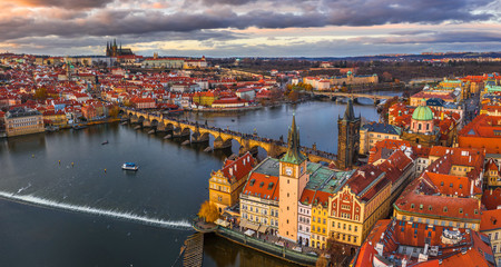 Acrylic Prints Prague Prague, Czech Republic - Aerial panoramic drone view of the world famous Charles Bridge (Karluv most) and St. Francis Of Assisi Church with a beautiful winter sunset. St. Vitus Cathedral at background