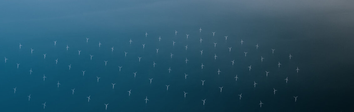 Windmills at the sea. Clean energy made by the wind. Photo in bird perspective. Offshore wind farm.