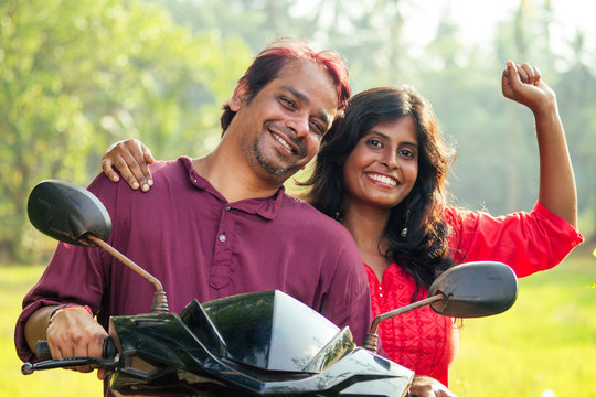 happy indian married couple riding on motorbike in tropical jungle in Goa India