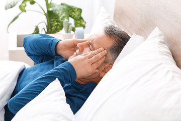 Mature man suffering from head ache while lying in bed