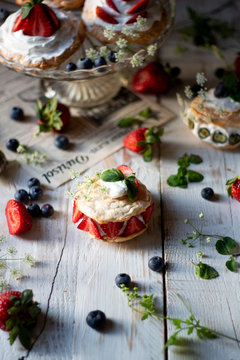Mini pavlovas on a cake holder and on white wooden table, sprinkled with fresh strawberries and blueberries, mint leafs and flowers