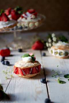 Delicate and rustic mini pavlova cakes with fresh strawberry and blueberry.
