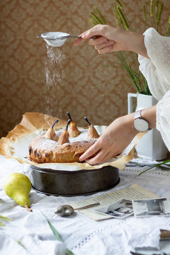 Rustic Pear poppy seed cake being sprinkled with powder sugar in front of the vintage wallpapper