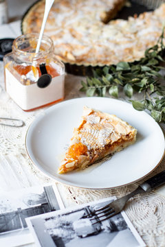 Rustic quince tart pie with almond flakes and powdered sugar on top.