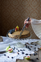 Women hand frosting zucchini chocolate cake with peanut butter topped with fresh fruits in front of the rustic wallpaper on wooden table with white table cloth.