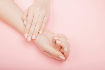 Stylish trendy manicure nail young woman hands on pink background, top view