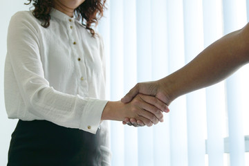 Businesswomen or professional executives shaking hands. Office setting. Welcome aboard or after good deal.