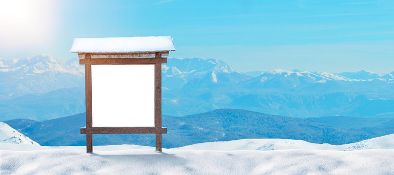 Ski resort sign, billboard mockup on a snowy mountain. Mountain peaks in the background. Copy space beside.