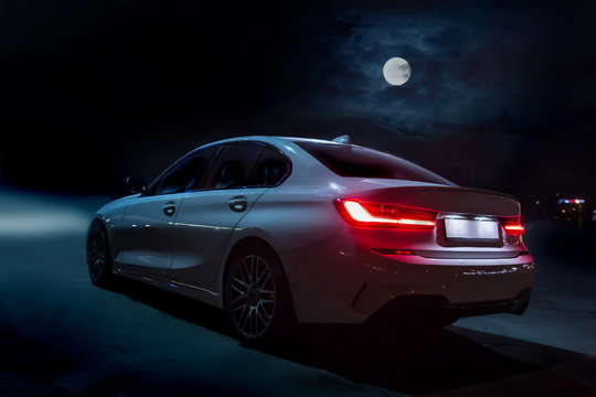 Car moves on the road on a moonlit night.
