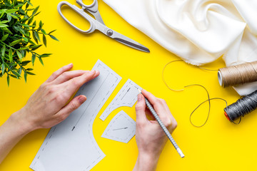 Tailor working. Women hands drawing patterns for clothes on yellow background top-down