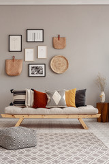 Dry flowers in white vase on small wooden table behind comfortable futon sofa with pillows