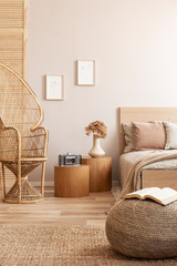 Open book on beige pouf in simple bedroom interior with peacock chair and single bed