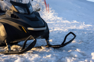 Snowdrift snowmobile on snow in ski resort. Off road vehicle with sleds outdoors