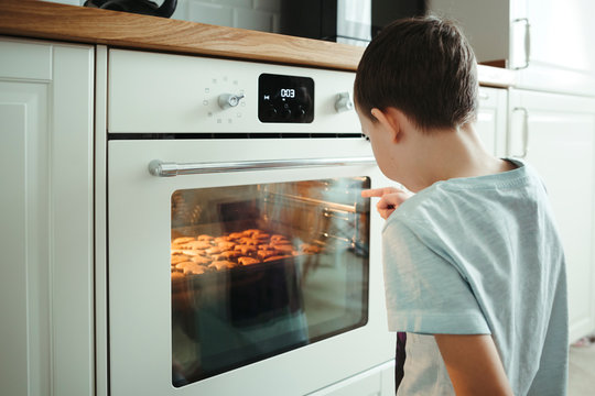 A young boy cooks cookies and patiently waiting next to a safe oven in the home interior.
