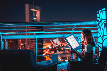 Asian girl reads the menu at the bar on the outdoor roof terrace overlooking the night city