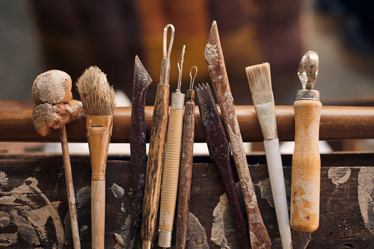 Tools for forming clay on  wooden background..