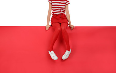 Woman wearing red tights and stylish shoes sitting on color background, closeup Fotomurales