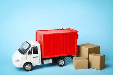 Toy truck with boxes on blue background, space for text. Logistics and wholesale concept