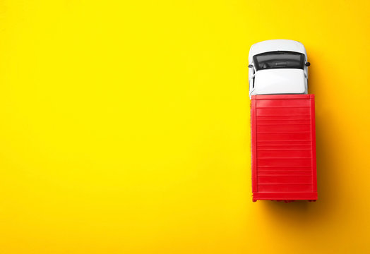 Top view of toy truck on yellow background, space for text. Logistics and wholesale concept