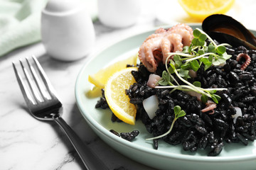 Delicious black risotto with seafood on white marble table, closeup