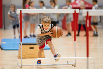 Young boy exercises with a basketball ball in a sports hall