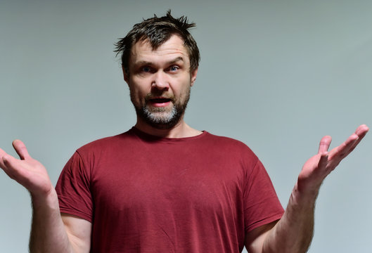 Portrait of a wild unkempt unshaven middle-aged man of 40 years in a burgundy t-shirt on a gray background. He stands right in front of the camera, talking, showing emotions. Waves his hands.