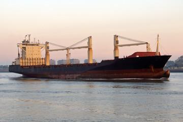 Feederschiff morgens bei der Einfahrt in den Hafen