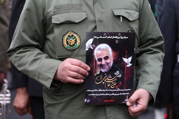 Iranian policeman man holds a picture of late General Qassem Soleimani in Tehran