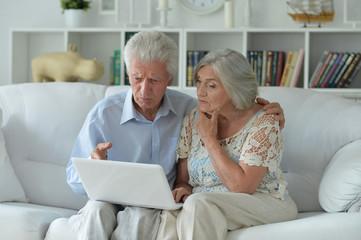 Portrait of senior couple using laptop at home Fototapete