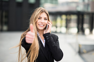 Smiling business woman talking on the phone and thumbs up