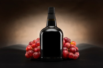 Fototapeta Czarna butelka czerwonego wina z winogronami packshot obraz