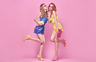 Wall Mural - Two Young carefree Woman in stylish playsuit having fun. Beautiful fashionable model girl in trendy summer outfit. Graceful friends with fashion hairstyle, make up on pink. Creative funny concept