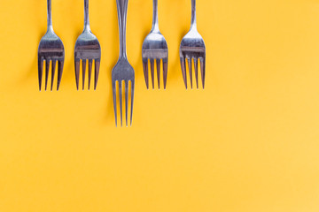 Holiday, table setting, cutlery . Minimal modern concept Luxury festive party background. Silver forks isolated on yellow background. vibrant summer party banner.Minimalism concept. Pop art style