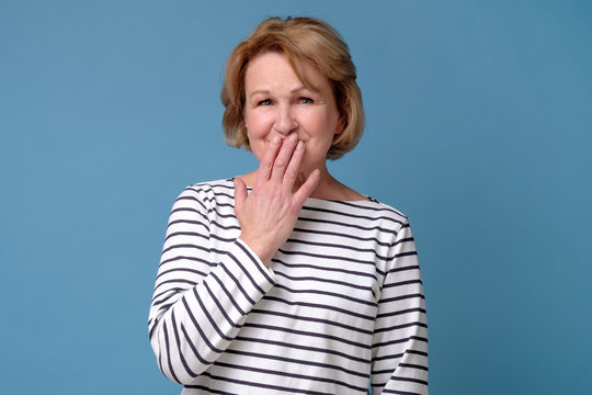 Surprised senior woman covering mouth with hand. She head a funny news about her coworker. Studio shot