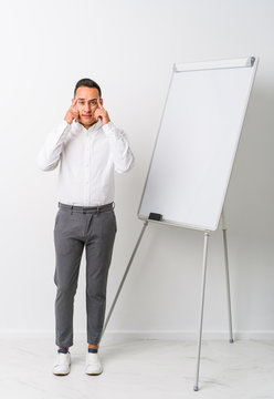Young latin coaching man with a whiteboard isolated focused on a task, keeping forefingers pointing head.