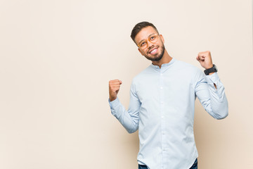 Young south-asian business man raising fist after a victory, winner concept.