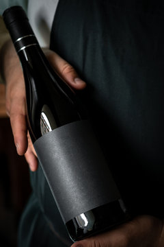 A full Bottle of wine in the hands of a male sommelier with a black label. Mock-up for red wine design.