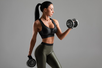 Fitness woman doing exercise for biceps on gray background. Muscular woman workout with dumbbells